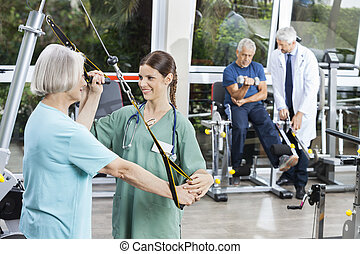 Nurse Assisting Senior Woman With Resistance Band Exercise