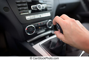Driver shifting the gear stick inside of car