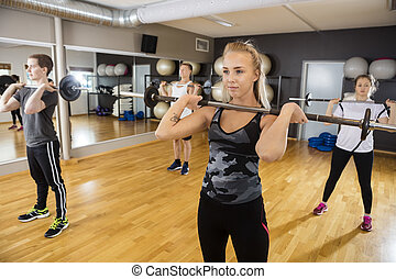 Friends Lifting Barbells While Standing In Health Club -...