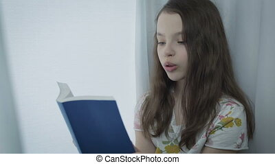 Beautiful little girl learns a poem by window - Beautiful...