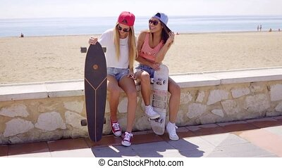 Two pretty friends hold skateboards on wall - Two pretty...