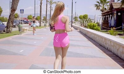 Beautiful jogger wearing pink shorts and top runs along a...
