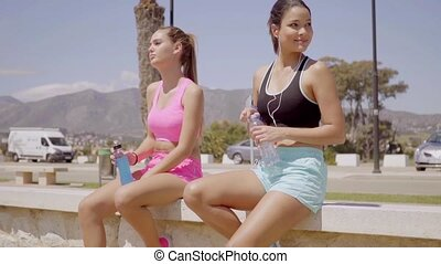 Two beautiful friends with water bottles relaxing - Two...