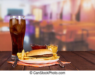 Hamburger, french fries, glass cola, sauces in background...