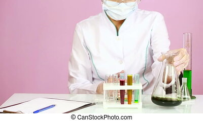 Female chemist comparing test tubes with chemicals...