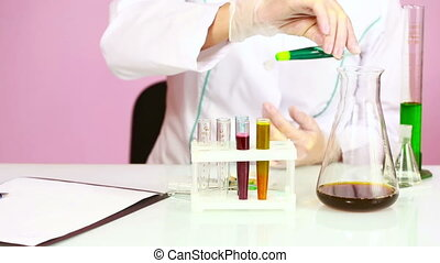 Female chemist comparing test tubes with chemicals....