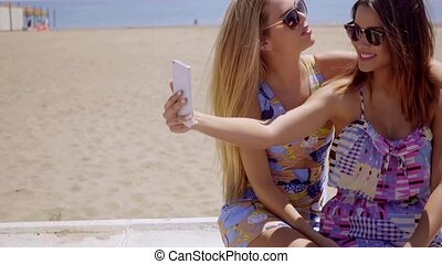Laughing young woman taking a selfie on their mobile phone...
