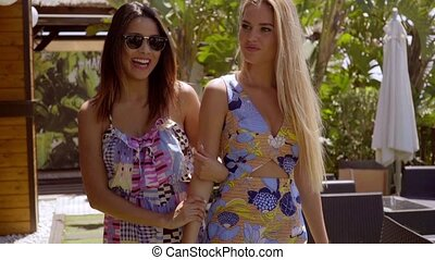 Two young women leaving an outdoor restaurant - Two trendy...