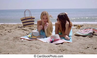 Two young women lying sun tanning on a beach - Two...