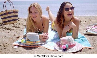 Two young women in bikinis enjoying the beach as they lie...