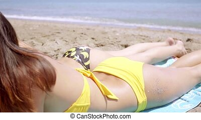 Close up of young woman sunbathing by her friend - Close up...