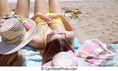 Two attractive young woman sunbathing in their bikinis at...