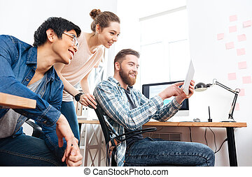 Three businesspeople working with tablet in office