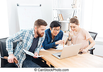 Three focused businesspeople working with laptop in office
