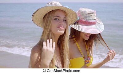 Two attractive women in trendy sunhats and bikinis walking...