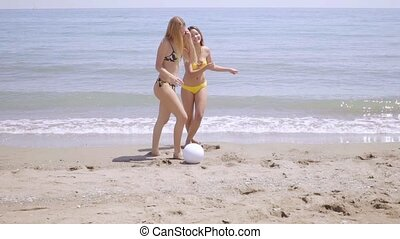 Two shapely young woman playing on a beach - Two shapely...