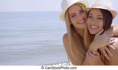 Fun spontaneous young women enjoying a hug of friendship as...