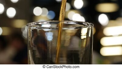 Pouring cola drink into glass closeup