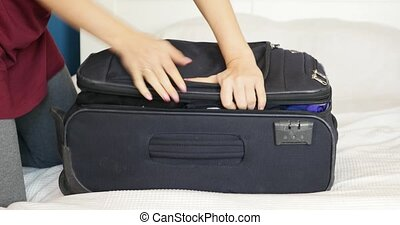 Young woman packing suitcase, trying to close it.