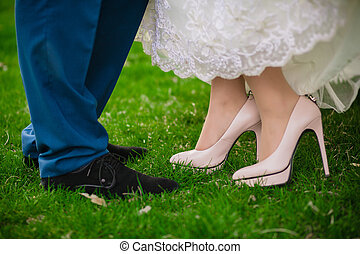 bride and groom standing on wooden bridge in park on grass