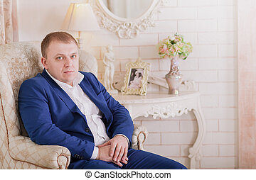 Gorgeous smiling groom. Handsome man in suite with a buttonhole sitting on window sill indoors