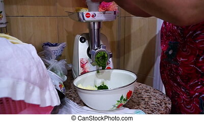 woman mincing beef and greens grinder in the kitchen hd