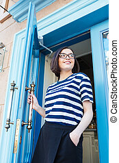 Smiling woman going out of cafe with blue door - Smiling...