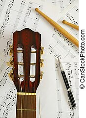 Guitar, drum sticks with pen on music score background. For...