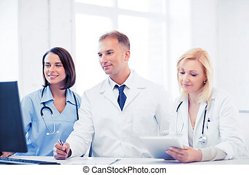 doctors looking at computer on meeting - healthcare, medical...