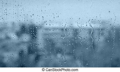 Rain drops on the window in blue