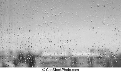 Downpour in black and white. Rain drops on the window.