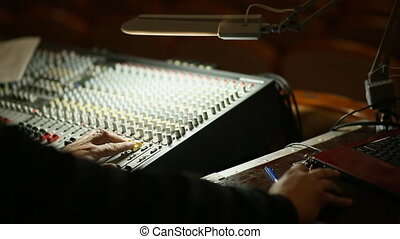 Professional's Hand Working On Audio Mixer In Studio.