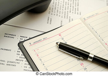 Phone with capped black pen on planner - Capped black pen on...