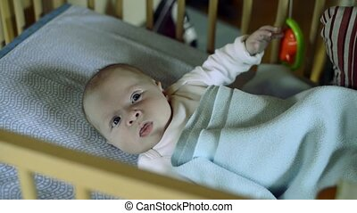 Little baby boy lying in wooden crib, moving