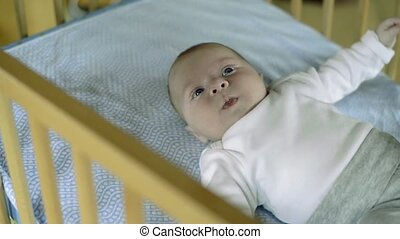 Little baby boy lying in wooden crib, moving - Cute little...