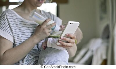 Unrecognizable mother feeding baby son, milk in bottle,...
