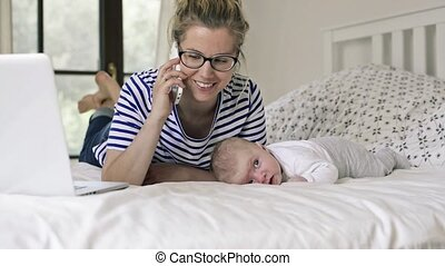 Young mother with baby son, lying on bed, smartphone - Young...