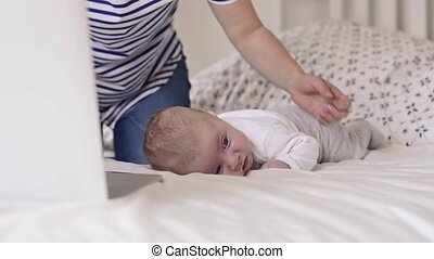 Unrecognizable mother with baby son, sitting on bed,...