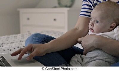 Unrecognizable mother with baby son, sitting on bed, working...