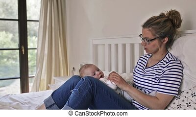 Young mother holding her newborn baby son, home bedroom -...