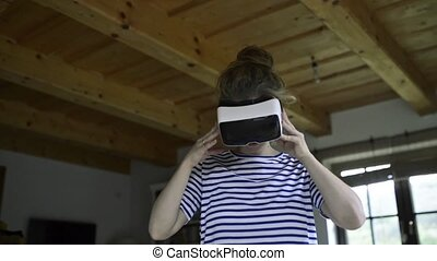 Woman wearing virtual reality goggles standing in living...