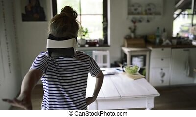 Woman wearing virtual reality goggles standing in a kitchen...