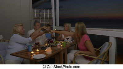 Family having meal on balcony in the evening - Mother, son...