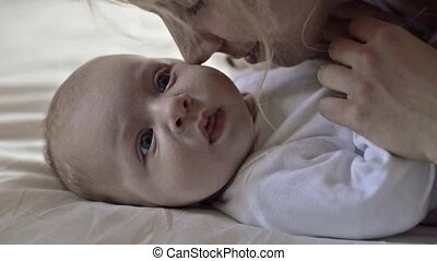 Baby boy lying on bed, held by his mother - Cute baby boy...