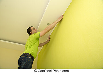 Man renovates room interior - Man constructor renovates room...