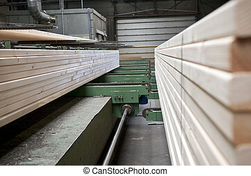 Lumber industry - Lumber coming of the conveyer belt in a...