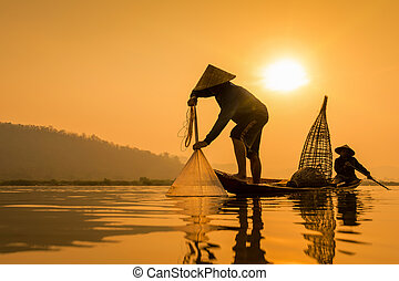 Silhouette of asia Fisherman on the boat on morning time...