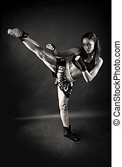 Beautiful girl kicking with the leg on black background