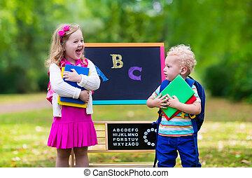 Children happy to be back to school. Preschooler girl and...