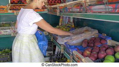 Choosing fruit in market - Woman choosing fruit in market